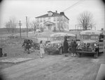 A group of people standing near two school buses stationed on a road in front of a farmhouse
