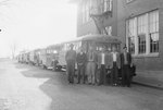 Group of six men standing in front of a line of school buses parked on the side of a street