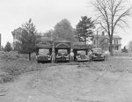 Four Robinson Produce Trucks, each of a different size and with their respective drivers standing to the side; photo taken from a distance by William Garber