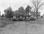 Four Robinson Produce Trucks, each of a different size and with their respective drivers standing to the side by William Garber