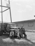 Four men posing in front of a company truck for the Grabole Company: Roofing and Spray Painting Contractors