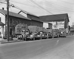 A row of company trucks for Triplett and Vehrencamp, a farming and hardware store. View without the drivers by William Garber