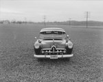 A private automobile parked alone in a field with road/power lines in the background. View from the front of the vehicle: Virginia license plate 614-853
