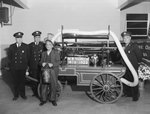 New Market Fire Department open house; view of four men posing next to a nineteenth-century fire truck