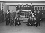 "A group of firemen/officers posing next to a nineteenth century ""fire truck"""