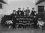 "A group of firemen/officers posing in front of a fire truck with flower bouquets on either side and a large sign that says ""New Market Fire Dept. New Market Va."""