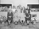 New Market Fire Department open house; a group of women posing in a kitchen with numerous flowers