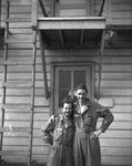 Two men in military uniforms posing against the outer wall of a building.