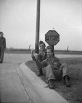 Three men in military uniform standing/sitting on the side of the road near a stop sign; they appear to be hitchiking.
