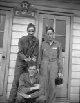 Three men in military uniform posing against the outer wall of a building; one is making an obscene gesture with his hands.