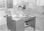 A man in a military uniform sitting at a desk.