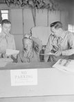 Three men in military uniform standing/sitting in an office