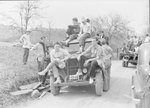 A large group of CCC workers piled onto a number of vehicles in a hilly, wooded area