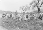 A group of CCC workers sitting in an overgrown field