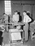 Three young men in the wood shop class at Timberville (High) School.