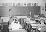 Broadway School, young boys and girls in a classroom facing the blackboard, where the teacher is using a pointer.