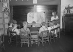 Broadway School, a group of young girls and boys sitting in a semi-circle in a classroom watching another young girl give a presentation at the blackboard. by William Garber
