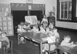Broadway School, a group of young boys and girls sitting at a table inside of a classroom.