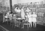 Broadway School, a group of young boys and girls looking at books in the library.