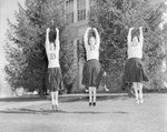 Broadway (High) School, three cheerleaders mid-jump as they practice a routine outside.