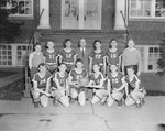 Broadway (High) School, men's basketball team posing in front of the school.