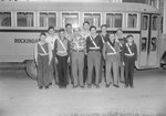 Broadway (High) School, group of young men and boys wearing Safety Patrol belts, with a school bus in the background.