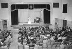 New Market High School, view from the back of the auditorium, where a woman and a man are playing the violin and piano on stage