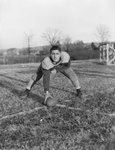 Massanutten Military Academy. A football player poses on the field with a football