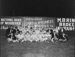 """Team photo of a men's baseball team with the letter """"E"""" on their uniforms. Fence of a baseball field advertising Woodstock businesses in the background. One player in the back row had """"Mount Jackson"""" on the front of his uniform"""