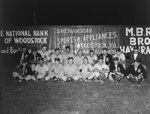 "Team photo of a men's baseball team with the letter ""E"" on their uniforms. Fence of a baseball field advertising Woodstock businesses in the background. One player in the back row had ""Mount Jackson"" on the front of his uniform"