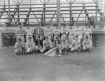 Team photo of the Grottoes Cardinals (probably of the Valley Twin County League or the Rockingham County League), men's baseball team, in front of the stands of a baseball field
