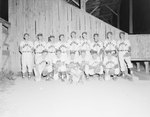 Team photo of the New Market Rebels, baseball team, in front of a fence at the game against the Harrisonburg Turks