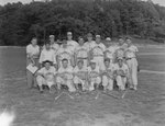 Team photo of the Romney men's baseball team, taken on the edge of a baseball field