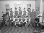 """Team photo of the men's baseball team for the Timberville Hatchery, with the letters """"GIs"""" on their uniforms. Photo taken inside of a home or office; one member in a wheelchair"""