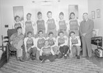 """Team photo of the men's baseball team for the Timberville Hatchery, with the letters """"GI's"""" on their uniforms. Photo taken inside of a home or office; one member is in a wheelchair"""