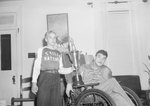 A baseball player of the Timberville Hatchery team posing with a man in a wheelchair and a large trophy