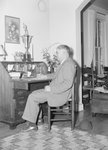 A man, presumably the coach or owner of the Timberville Hatchery baseball team, sitting at a desk and looking at a large trophy