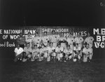 Team photo of the Woodstock men's baseball team(probably Woodstock River Bandits of the Valley League), with a baseball field's fence in the background advertising Woodstock businesses