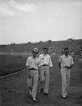 Three men walking on the edge of a baseball field