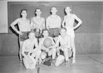 Seven men posing in a gym before or after playing a game of basketball