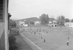 View of a large number of people on a sports field, taken from an upper story window and from a distance
