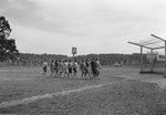 Group of young women crossing a large sports field