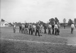 A group of men walking across a large sports field, followed by a man carrying a ball, possibly a basketball