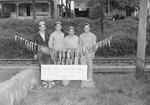"""Four men standing behind a long string of fish that is tied to two trees, and a sign that says: """"Blair, 18"""" 1-14 (and) 17.5 1-12; Max, 16.5-1-5.5; Calvin, 18""""-1-14; Paul, 18"""" 2-3.5 (and) 18"""" 1-15.5. Big Stoney Creek. 1948."""""""