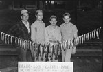"""Close up four men standing behind a long string of fish that is tied to two trees, and a sign that says: """"Blair, 18"""" 1-14 (and) 17.5 1-12; Max, 16.5-1-5.5; Calvin, 18""""-1-14; Paul, 18"""" 2-3.5 (and) 18"""" 1-15.5. Big Stoney Creek. 1948."""""""