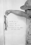 """A man holding a fish up to a blackboard, upon which is written: """"Brook Trout, Length 13"""", Weight 15oz, Captured by Paul Myers, 20 April 1948."""""""