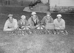 Five men laying on their stomachs in the grass, with three small baskets and a large number of fish on the ground in front of them