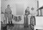 A man and a boy standing in a kitchen with a large string of fish