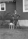 A man standing outside of a home with his dog and a gun, holding a long rope with a number of birds strung to it