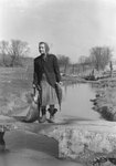 A woman standing on a small bridge holding a fish that is roughly half the size of her body